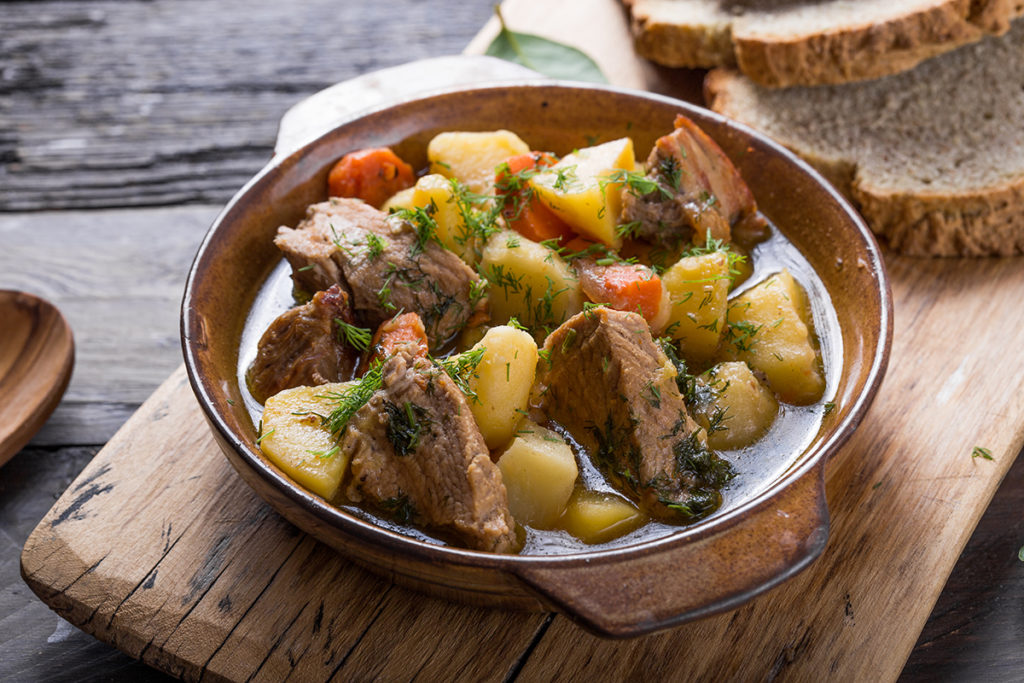 Potato Stew. Irish dinner. Beef meat stewed with potatoes, carrots and soda bread on wooden background, top view, copy space. Homemade winter comfort food - slow cooked